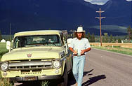 thumbnail link to photograph Steve McQueen by pick up truck mountains behind