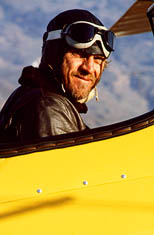 thumbnail link to photograph of Steves miling in cockpit, leather flying helmet